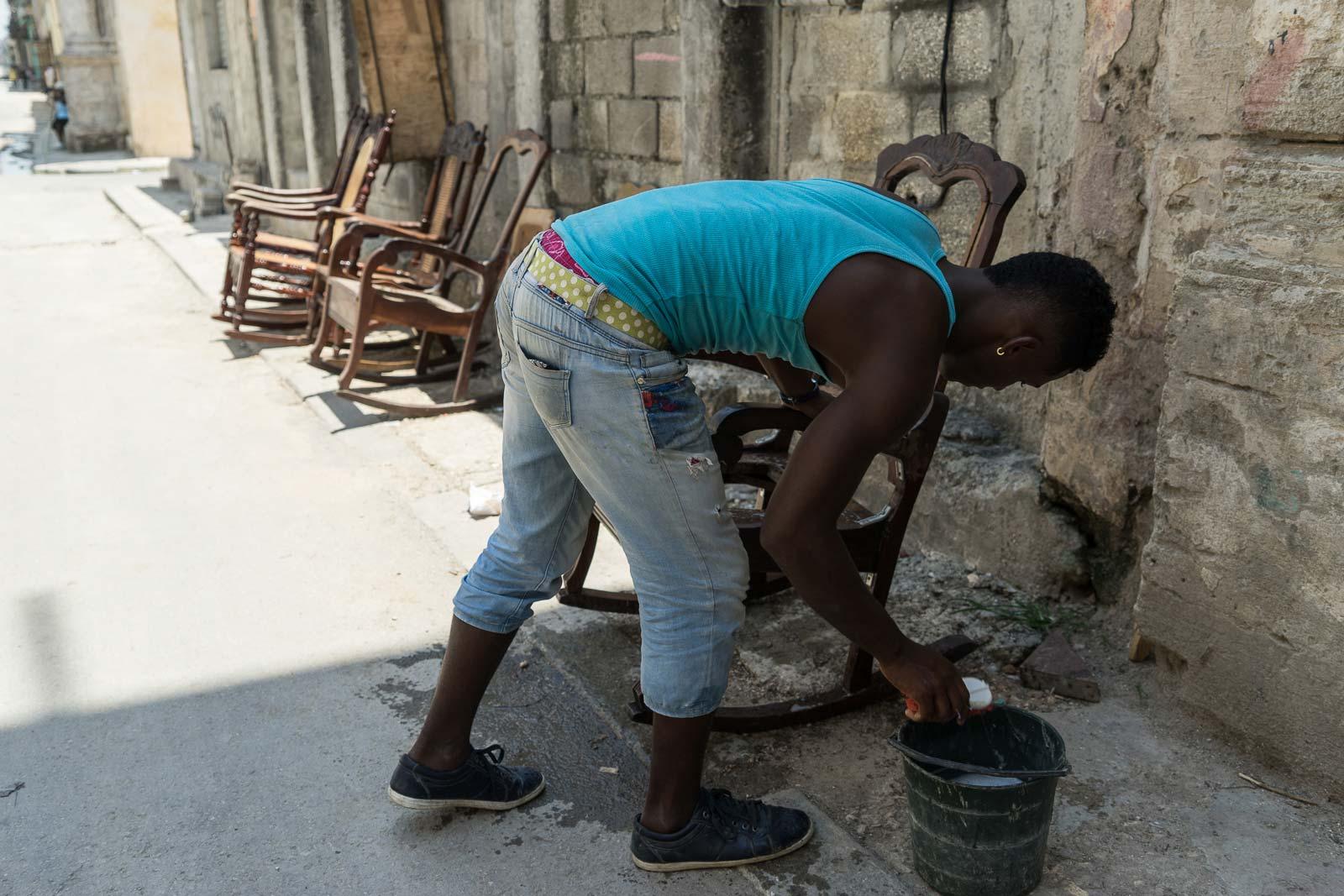 Ci-dessus, un jeune homme nettoie des chaises à vendre sans se préoccuper le moindrement du photographe.